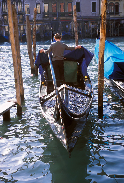 Morning on the Grand Canal: lone gondolier, seen from behind, uncovers his gondola in preparation for a day's work.