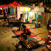 A vendor and her daughter look after their stall at the night market on Quai Fa Ngum on the banks of the Mekong in Vientiane, Laos.