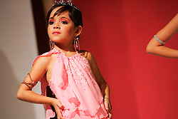 Maria Luisa Rodriguez, a participant in the Miss Mini Modelo Venezuela pageant, waits backstage before the start of the pageant.  The pageant is for girls aged 6-10. Beauty pageants for little girls are fairly common and very accepted in Venezuela. Girls aged 6-10 often spend months or years taking all sorts of beauty school classes, ranging from runway walking to makeup to etiquette. The families spend thousands of dollars on preparing their girls for the pageants ; they have to pay for beauty school classes, a competition entrance fee, dresses and many other expenses.  The world of beauty pageants is said to be very corrupt, where the highest bidder is the surest winner.
