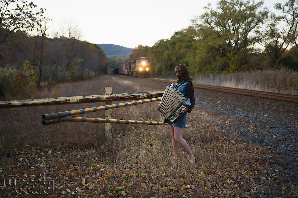 Young woman playing accordion next to train tracks