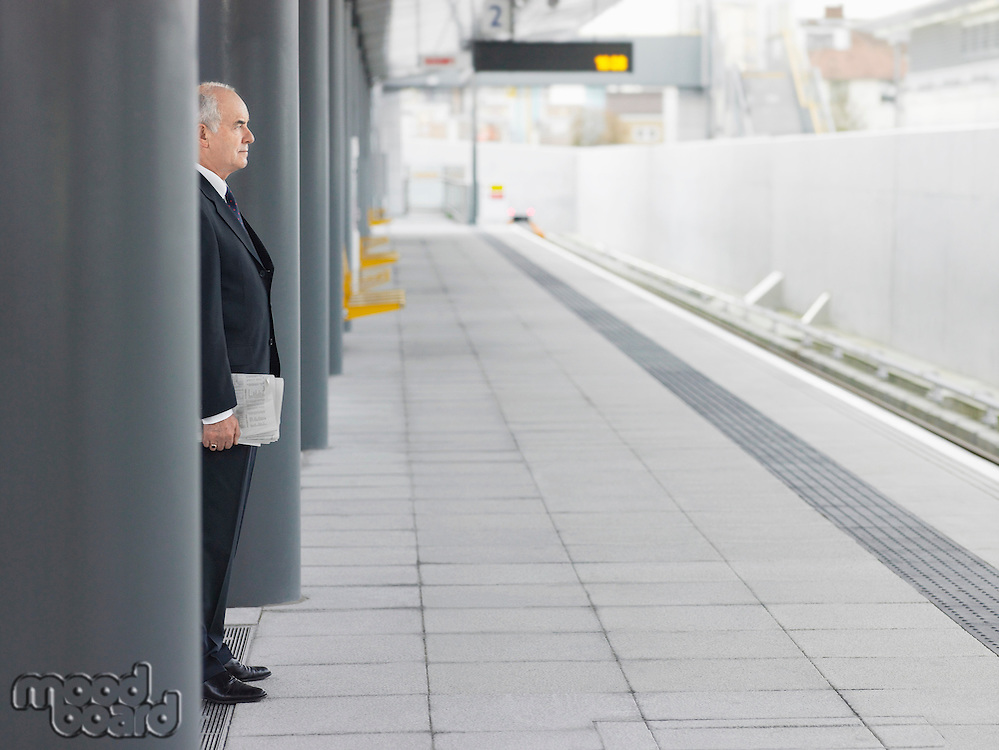 Mature Businessman standing Waiting at empty Train Station side view