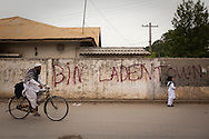 Residents of Bilal Town pass recently spray-painted graffiti in Bilal Town, on the road leading to the compound where Osama Bin Laden was killed by US forces, on 6 May, 2011, in Abbottabad, Pakistan.  The operation, code-named Operation Neptune Spear, was launched from neighbouring Afghanistan by Seal Team Six. U.S. forces took bin Laden's body to Afghanistan for identification, then dumped it the Arabian Sea. Pakistan has since been widely suspected as having prior knowledge of his whereabouts as the compound was less than a kilometre from the country's biggest military academy. Osama bin Laden was allegedly responsible for supporting the bombing of the US Embassy in Nairobi, Kenya, the attack on the USS Cole and the suicidal attacks of September 11, 2001 in the US. (Photo by Warrick Page)