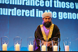 © Licensed to London News Pictures.  28/01/2013. LONDON, UK. Shaykh Ibrahim Mogra (pictured), Assistant Secretary General of the Muslim Council of Great Britain, lights a candle at the Holocaust Memorial Day 2013 UK Commemoration event held today in the QE2 conference centre. The annual event is held to remember genocides across the globe including the holocaust, Bosnia, Cambodia, Rwanda and Darfur.  Photo credit :  Cliff Hide/LNP
