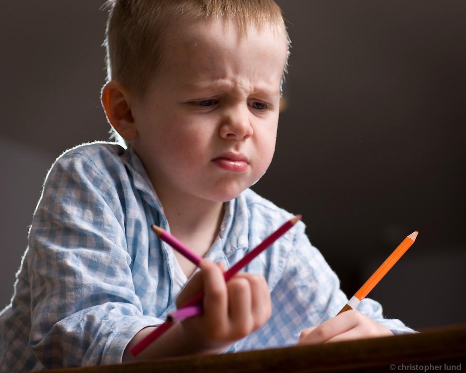 Ari Carl að lita við stofuborðið heima í sandavaði. Young boy waring pajamas coloring at home.