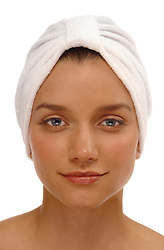 Head shot of a pretty young woman with a spa turban on a white background