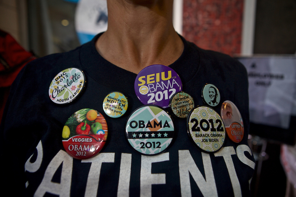 A women shows her support of Pres. Barack Obama with pins across her chest as she watches a live taping of Hardball with Chris Matthews at the MSNBC EpiCenter during the 2012 Democratic National Convention on Monday, September 3, 2012 in Charlotte, NC.