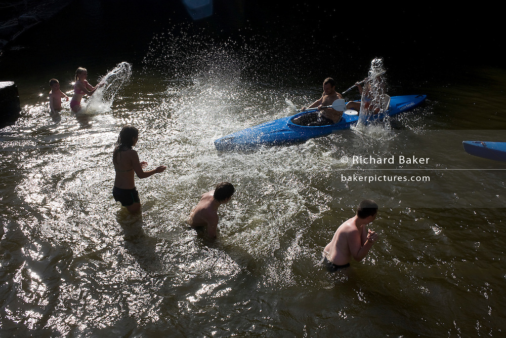Throwing water, bathers splash canoeists as they paddle into a weir on the Belgian Ardennes region River Lesse, near Dinant.