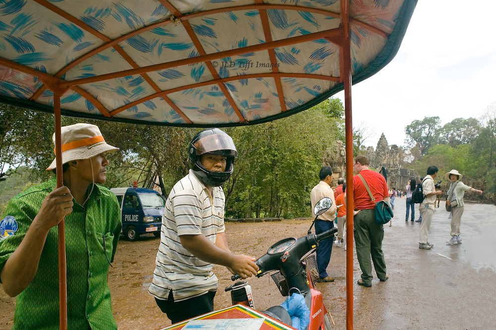 Passenger's view from a Siem Reap tuktuk, beneath its roof,  with driver (in helmet), guide (in green official guide's shirt) and a scattering of other tourists on foot deciding where to begin their explorations.   The pavement is rain - slicked.