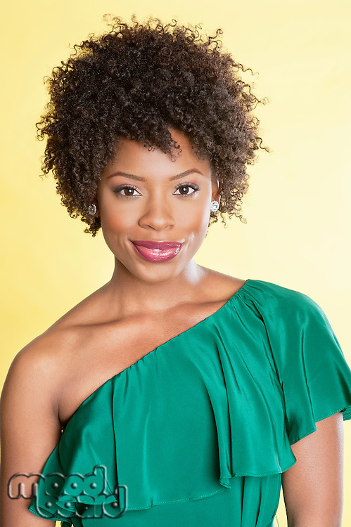 Portrait of an elegant African American in an off shoulder dress smiling over colored background