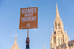 © Licensed to London News Pictures. 24/01/2015. Westminster, UK. A demonstrator's placard held aloft as they stage a mass protest against government plans to spend £100 billion replacing Trident, the UK's Cold War nuclear weapons system.  They encircled government and parliament buildings with a peace scarf knitted by thousands of people. Photo credit : Stephen Chung/LNP