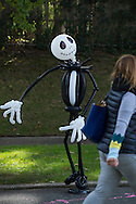 Merrick, New York, USA. October 29, 2016. A spooky Jack Skellington character made of black and white balloons appears to be looking at a girl walking past it, at the 2016 annual Merrick Spooktacular hosted in part by the North and Central Merrick Civic Association (NCMCA). The holiday party was at Fraser Park.
