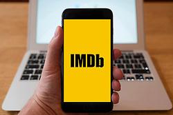 Using iPhone smartphone to display logo of IMDB, the Internet Movie Database ,