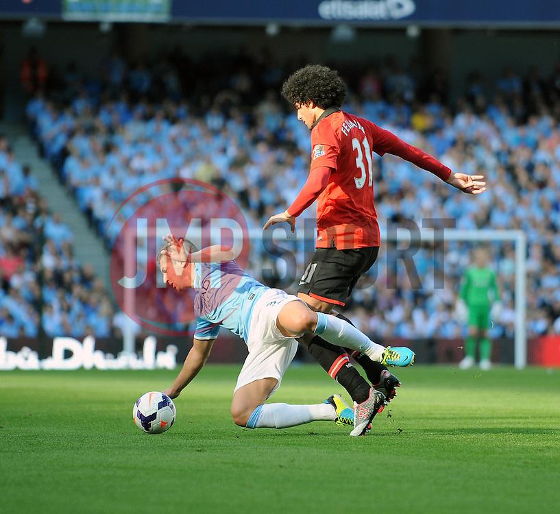 Manchester United's Marouane Fellaini fouls Manchester City's Matija Nastasic - Photo mandatory by-line: Dougie Allward/JMP - Tel: Mobile: 07966 386802 22/09/2013 - SPORT - FOOTBALL - City of Manchester Stadium - Manchester - Manchester City V Manchester United - Barclays Premier League