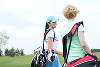 Smiling female golfer talking to friend at golf course