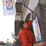 Slager Peter de Jong hangt vlag buiten zijn winkel