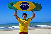 "Kite surfer with the brazilian flag painted on the board with ""praia e vento"" (beach and wind) instead of ""ordem e progresso""  in prainha beach near fortaleza"