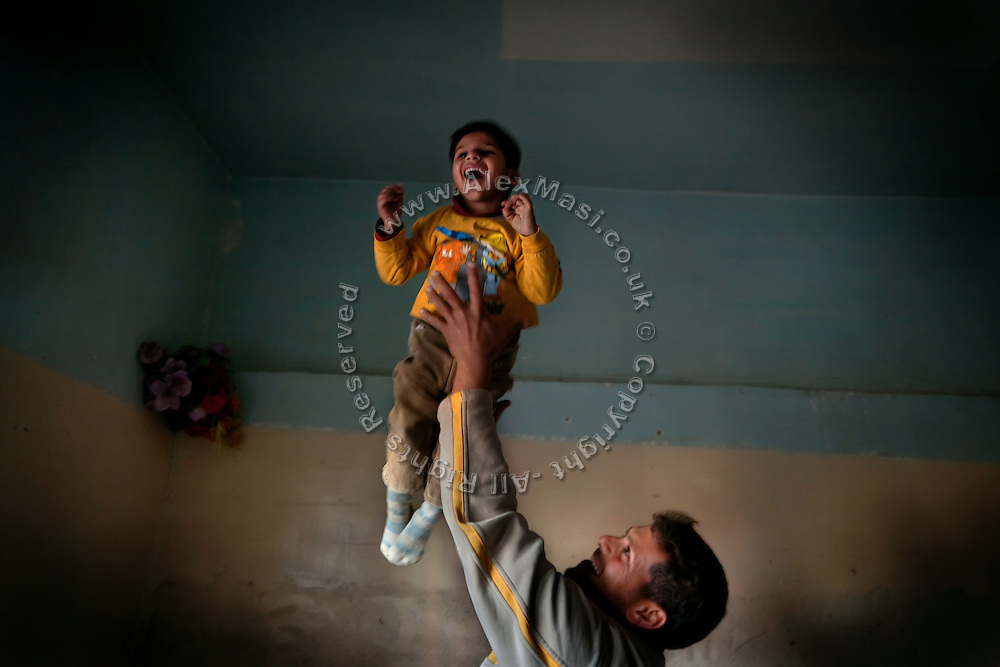 Mohammed Thiab, a young 25-year-old father, is playing with Jasim, 5, one of his two children affected by neurological disorders, on the floor of their home in Fallujah, Iraq. The children have a healthy 8-year-old sister, Sauusan, born before the 2004 US-led battles, who regularly helps the parents in assisting her sick siblings. The parents and their relatives have no history of birth defects.