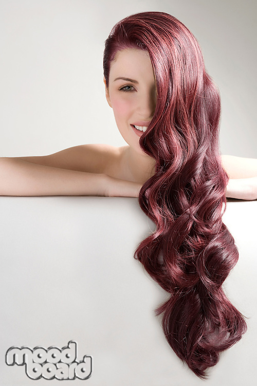Beautiful woman with long red dyed hair against gray background