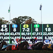 Race horses and jockey's pass the betting board display during racing at Belmont Park during the Jockey Club Gold Cup Day, Belmont Park, New York. USA. 28th September 2013. Photo Tim Clayton