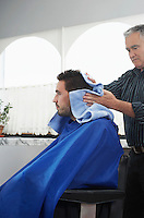 Barber preparing man for haircut in barber shop