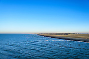 Nederland, Noord-Holland, Gemeente Schoorl, 11-12-2013; Petten, Hondsbossche en Pettemer Zeewering gezien vanuit zee, richting Petten.<br /> De dijk is aangelegd als zeewering nadat de oorsrponkelijke duinen weggeslagen waren. Door erosie kalven de duinen langs de kust steeds verder af, de dijk steekt daardoor steeds meer uit in zee.<br /> Hondsbossche and Pettemer seawall seen from the sea in the direction of the village Petten<br /> The dike was built as a seawall after the primal dunes were washed away. Because of erosion the dunes decrease in size, therefore the sewall sticks more and more out into the sea.<br /> luchtfoto (toeslag op standard tarieven);<br /> aerial photo (additional fee required);<br /> copyright foto/photo Siebe Swart