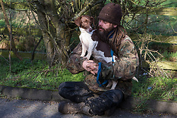 Denham, UK. 11 February, 2020. An environmental activist opposed to HS2 sits with a dog at the roadside at Denham in the Colne Valley. Contractors working on behalf of HS2 are rerouting electricity pylons through a nearby Site of Metropolitan Importance for Nature Conservation (SMI) in conjunction with the high-speed rail link.