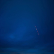 """Zipper in the Sky."" View of the Hudson from Cold Spring. Light stripe in sky is from lights of a plane made with long exposure."
