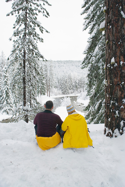 Couple sitting in snow enjoying view of Wenatchee River Washington USA.