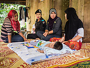 17 JUNE 2015 - RANGAE, NARATHIWAT, THAILAND:  Thai Army Ranger 2nd Lt MONTHA SOMPIASERT, center, and two medics from her unit talk to a Thai Muslim woman in her home. Her son was born with birth defects. The Rangers bring them food and perform wellness checks as a part of the Rangers' outreach program. There are 5 platoons of women Rangers serving in Thailand's restive Deep South. They generally perform security missions at large public events and do public outreach missions, like home wellness checks and delivering food and medicine into rural communities. The medics frequently work in civilian clothes because the Rangers found people are more relaxed around them when they're in civilian clothes. About 6,000 people have been killed in sectarian violence in Thailand's three southern provinces of Narathiwat, Pattani and Yala since a Muslim insurgency started in 2004. Attacks usually spike during religious holidays. Insurgents are fighting for more autonomy from the central government in Bangkok.    PHOTO BY JACK KURTZ
