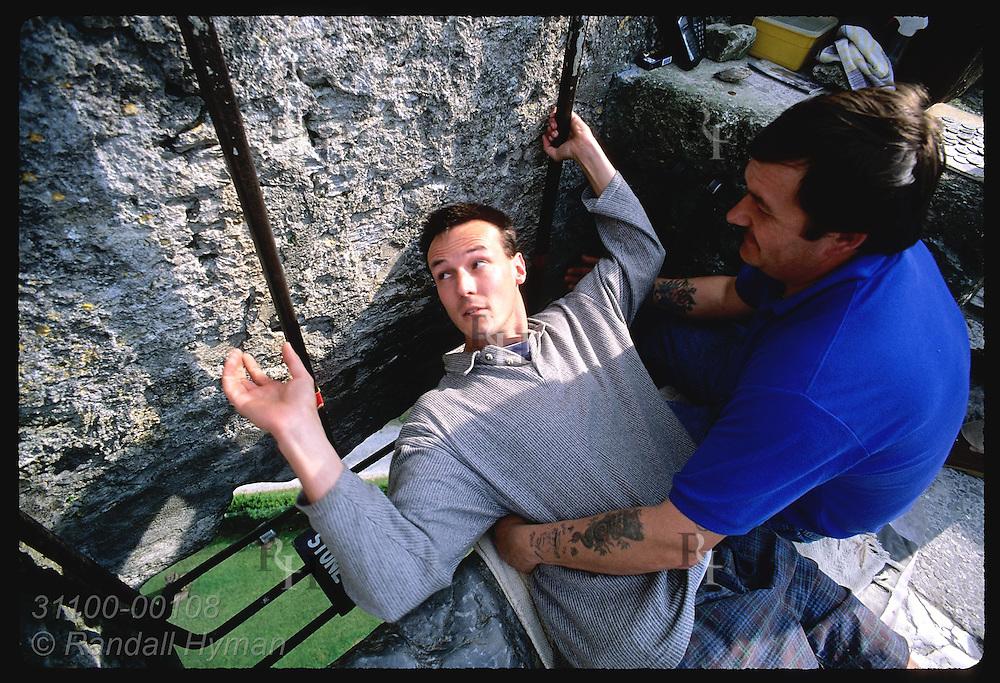 'Holder' Nigel Barrows helps man lean back to kiss Blarney Stone atop 130' Blarney Castle. Ireland