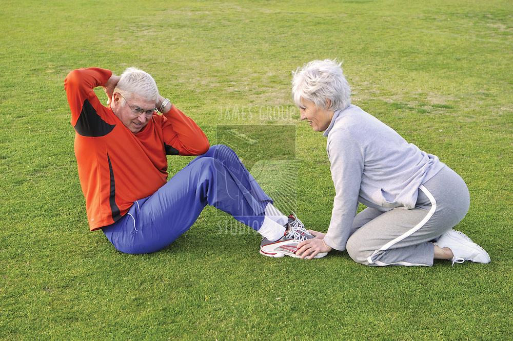 Senior couple doing sit ups on grass