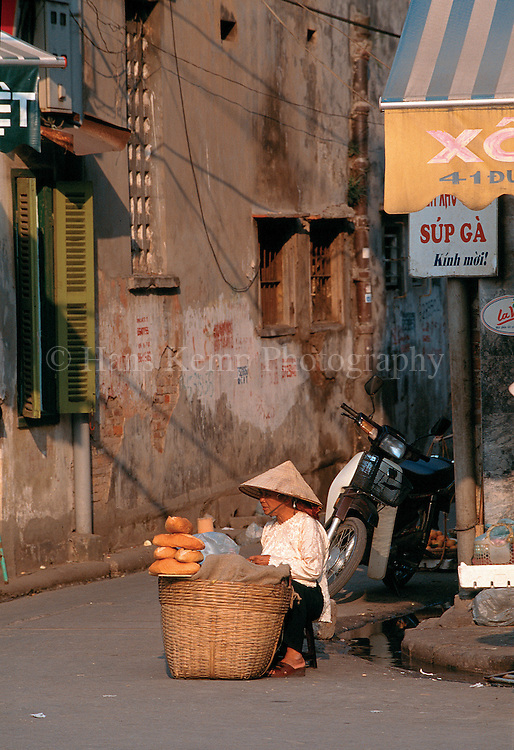 A woman sells French style bread on a streetcorner in Hanoi.