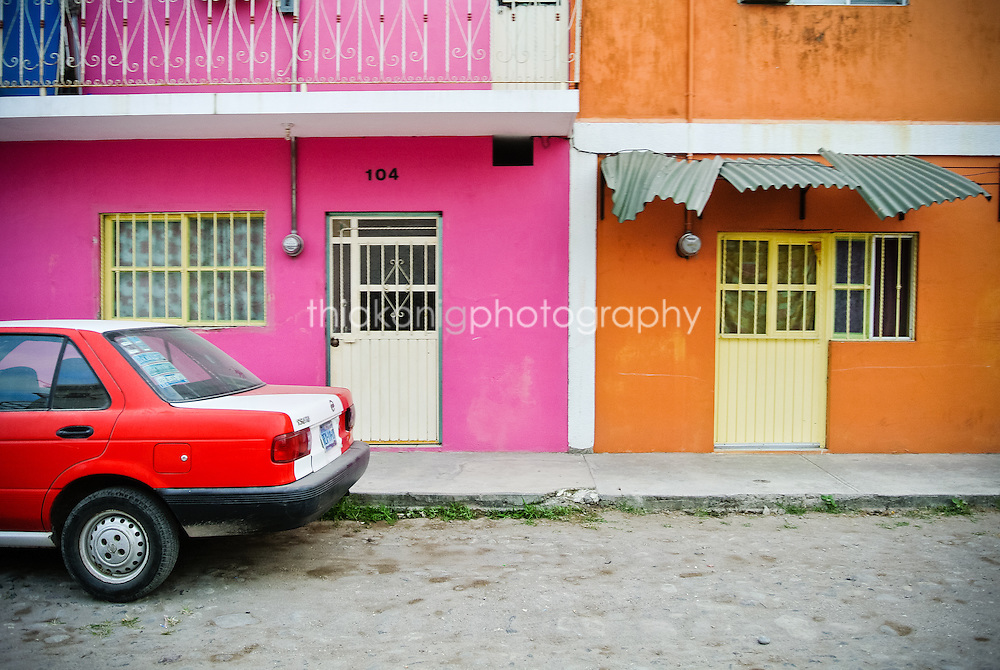 The crazy colors of Mexico. Neighbors paint their apartments pink and orange, with a red car parked out front, San Blass, Mexico