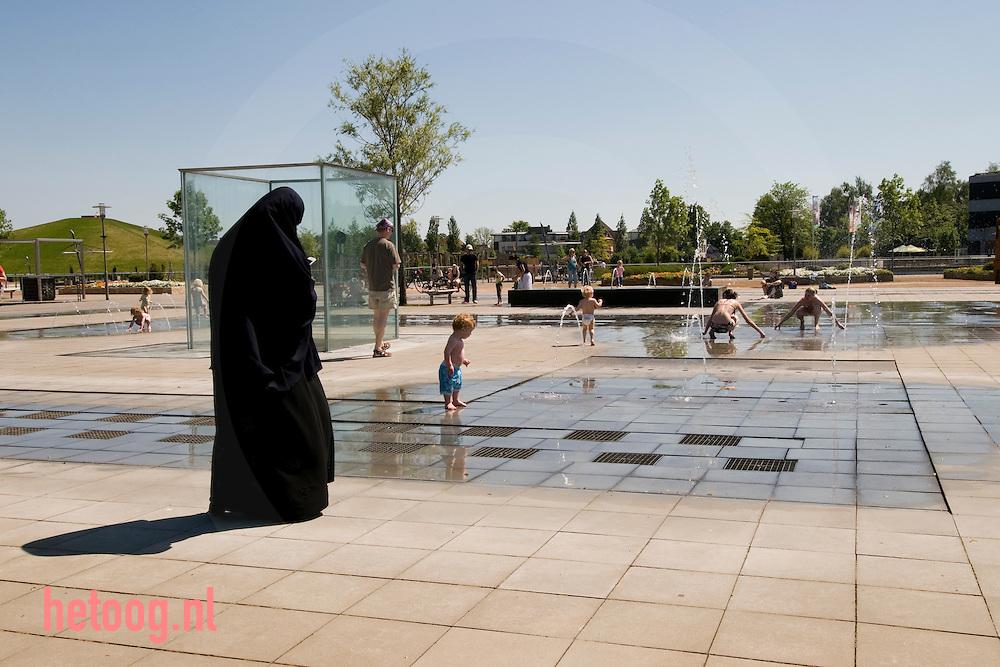 een islamitisch geklede vrouw kijkt hoe haar kind met water speelt