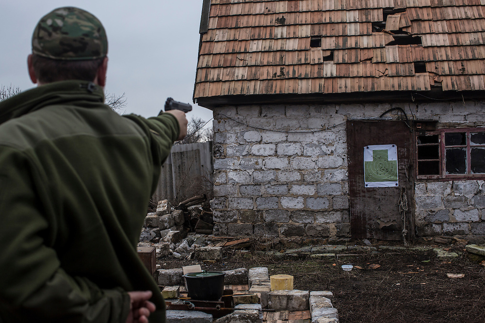 Gennady Lysenko, a military chaplain, shoots a gun at a target on Saturday, February 13, 2016 in Zaitseve, Ukraine.