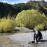 Panning for gold on the Arrow River, Arrowtown. Arrowtown is the much visited, historic, 4-season, southern hemisphere holiday destination, located only 20 minutes drive from Queenstown, South Island, New Zealand..Arrowtown is a former gold-mining town built on the banks of the Arrow River, once a rich source of gold in the 1860's and now a sophisticated, multi-cultural town catering to the refined tastes of its visitors from around the globe. Arrowtown offers an ambiance with its shops, restaurants, cafes, offices and galleries located within a tight precinct.  5th April 2011.  Photo Tim Clayton.