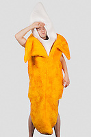 Tired man in banana costume against gray background