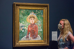 "© Licensed to London News Pictures. 04/08/2020. LONDON, UK. A staff member poses with ""Young Girl on the Grass, the Red Bodice (Mademoiselle Isabelle Lambert"", 1895, by Berthe Morisot. Preview of ""Gauguin and the Impressionists : Masterpieces from the Ordrupgaard Collection"" at the Royal Academy of Arts in Piccadilly.  60 works from a collection of Impressionist paintings, assembled by wealthy Danish couple Wilhelm and Henny Hansen, are on show 7 August to 18 October 2020, and includes masterpieces by Gauguin, Degas, Monet, Morisot, Pissarro, Renoir and Sisley.  Photo credit: Stephen Chung/LNP"