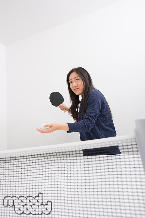 Beautiful young woman preparing to serve ping pong ball