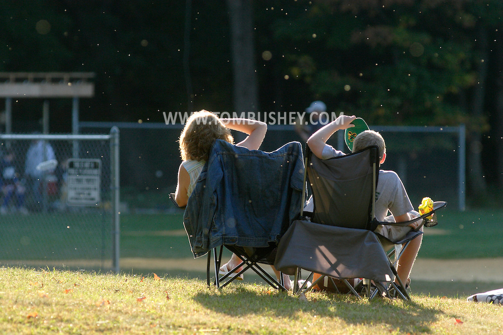 Two spectators shade their eyes as they sit in lawn chairs to watch SUNY Orange play Dutchess Community College in a fall baseball game on Oct. 7, 2007. Small insects backlit by the late afternoon sun are visible in the air.