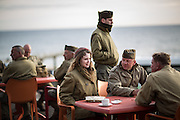 Reenactor having a warm coffee on a cold dawn Omaha beach just 70 year after the D-Day