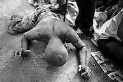 """15 MARCH 2014 - NAKHON CHAI SI, NAKHON PATHOM, THAILAND: A man in a trance crawls to the stage at the Wat Bang Phra tattoo festival. Wat Bang Phra is the best known """"Sak Yant"""" tattoo temple in Thailand. It's located in Nakhon Pathom province, about 40 miles from Bangkok. The tattoos are given with hollow stainless steel needles and are thought to possess magical powers of protection. The tattoos, which are given by Buddhist monks, are popular with soldiers, policeman and gangsters, people who generally live in harm's way. The tattoo must be activated to remain powerful and the annual Wai Khru Ceremony (tattoo festival) at the temple draws thousands of devotees who come to the temple to activate or renew the tattoos. People go into trance like states and then assume the personality of their tattoo, so people with tiger tattoos assume the personality of a tiger, people with monkey tattoos take on the personality of a monkey and so on. In recent years the tattoo festival has become popular with tourists who make the trip to Nakorn Pathom province to see a side of """"exotic"""" Thailand.   PHOTO BY JACK KURTZ"""