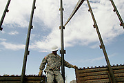 Staff Sargeant Douglas Mecham of the 115th Group of the Utah National Guard works building a new barrier fence along the US-Mexico border near San Luis, AZ on Wednesday, June 7, 2006.<br />
