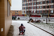 A boy riding on three wheel at the courtyard of the pastoral centre of the Salesians of Don Bosco mission, surrounded by a wall - at Lunik IX in Kosice. The LUNIK IX housing complex - populated with almost 100% Roma inhabitans - in the western-central part of the city of Kosice located in Eastern Slovakia. The living conditions in Lunik IX are partly very bad and many people do not have electricity, water or gas. Some of the buildings are completely devasted. Lunik IX has officially 6542 registered (12/2015) inhabitants and almost all of them are of Roma ethnicity.