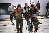 Libyan rebels attack Bab Al Azizyia,  Gadhafi's headquarters compound in Tripoli. Under fierce gunfire, a wounded fighter is evacuated by his comrades on Al Jala'a avenue during the assault on the compound.