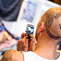 Manchester, UK - 4 August 2012: a tattoed man takes a picture with his mobile phone during the Manchester Tattoo Show, one of the most popular conventions of the UK tattoo community.