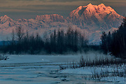 First light on Mt. Hunter which sits next to Mt Denali with the frozen Susitna River in the foreground.