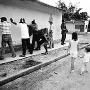Two young children walk past a police patrol as it searches a group of menfolk for ID and weapons in Saravena, Aruaca, Colombia. Two rebel groups; the ELN and FARC as well as the rightwing AUC are all fighting for control of this oil rich region.<br />
