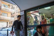 Roma, 27/04/2016: padre e figlia cinesi passano davanti un negozio di stoffe indiane, Torpignattara.<br /> &copy;Andrea Sabbadini