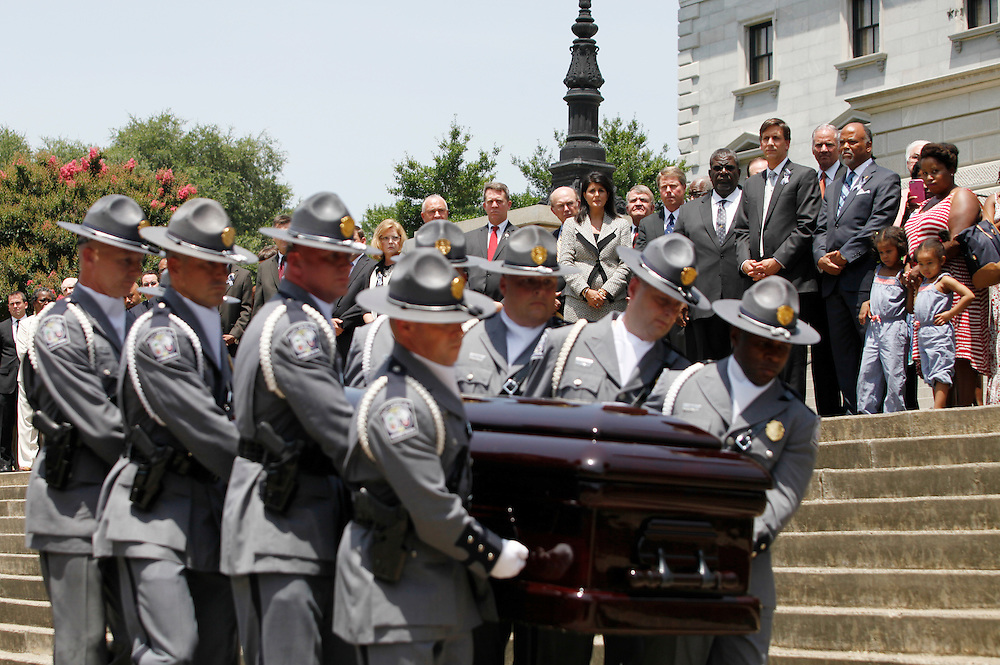 Gov. Nikki Haley, center, stands by as nine troopers carry state Sen. Clementa Pinckney's casket into the S.C. Statehouse in Columbia on Wednesday, a week after Pinckney and eight other people were fatally shot at Emanuel AME Church in downtown Charleston. (ANDREW KNAPP/STAFF)